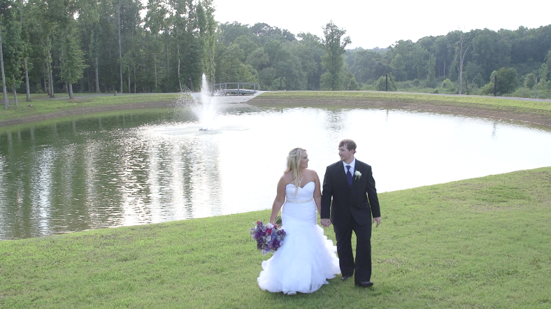 Bride and Groom walking in front of water fountain at Camp Meadowbrook